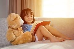 Libro di lettura cinese asiatico sorridente della bambina con l'orsacchiotto Fotografia Stock