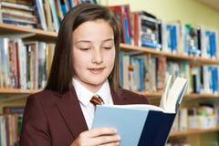 Libro di lettura d'uso dell'uniforme scolastico della ragazza in biblioteca Fotografia Stock Libera da Diritti