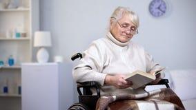 Libro di lettura d'uso handicappato turbato degli occhiali della donna, solitudine nella vecchiaia immagini stock libere da diritti