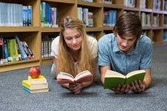 Libro di lettura degli studenti che si trova sul pavimento delle biblioteche Fotografia Stock Libera da Diritti