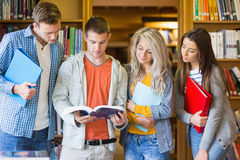 Libro di lettura degli studenti contro lo scaffale per libri in biblioteca Fotografia Stock