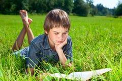 Libro di lettura del bambino all'aperto Immagini Stock