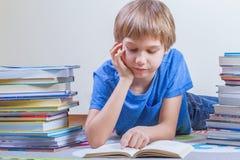 Libro di lettura del bambino fra le pile di libri Immagine Stock