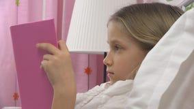 Libro di lettura del bambino a letto, bambino che studia, ragazza che impara nella camera da letto dopo il sonno immagini stock