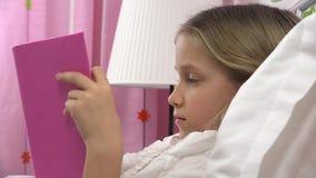 Libro di lettura del bambino a letto, bambino che studia, ragazza che impara nella camera da letto dopo il sonno stock footage
