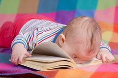 Libro di lettura del bambino su fondo variopinto Fotografie Stock Libere da Diritti