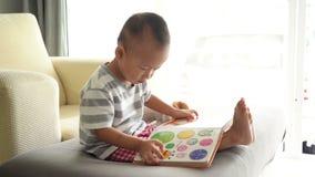 Libro di lettura del bambino sul sofà stock footage