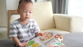 Libro di lettura del bambino sul sofà archivi video