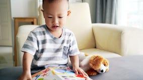 Libro di lettura del bambino sul sofà video d archivio