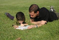 Libro di lettura del figlio e del padre Immagini Stock Libere da Diritti