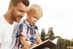 Libro di lettura del figlio e del padre Fotografia Stock Libera da Diritti