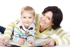Libro di lettura del figlio e della madre insieme sopra bianco Fotografie Stock Libere da Diritti