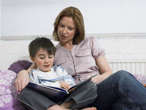 Libro di lettura del figlio e della madre sul letto Fotografie Stock