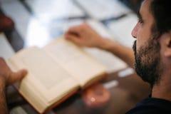 Libro di lettura del giovane, imparante sulla tavola Fotografie Stock