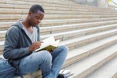 Libro di lettura del giovane nello spazio della copia della città universitaria Fotografia Stock