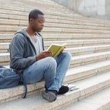 Libro di lettura del giovane nello spazio della copia della città universitaria Fotografie Stock