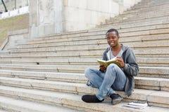 Libro di lettura del giovane nello spazio della copia della città universitaria Immagini Stock