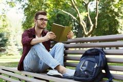 Libro di lettura del giovane nello spazio della copia del parco Fotografia Stock Libera da Diritti