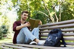 Libro di lettura del giovane nello spazio della copia del parco Immagini Stock