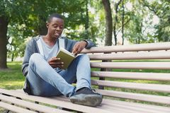 Libro di lettura del giovane nello spazio della copia del parco Fotografia Stock