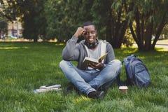 Libro di lettura del giovane nello spazio della copia del parco Fotografie Stock Libere da Diritti