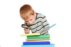 Libro di lettura del ragazzino con la lente d'ingrandimento Immagine Stock