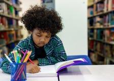 Libro di lettura del ragazzino nella biblioteca Fotografia Stock Libera da Diritti