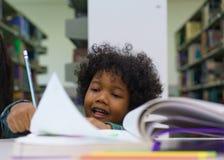 Libro di lettura del ragazzino nella biblioteca Fotografia Stock