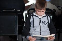 Libro di lettura del ragazzo alla stazione immagine stock