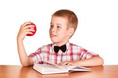 Libro di lettura del ragazzo alla tavola, Apple rosso disponibile, isolato su bianco Fotografia Stock Libera da Diritti