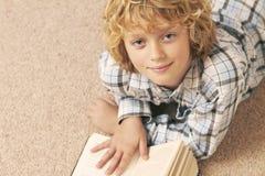 Libro di lettura del ragazzo in camera da letto Immagini Stock