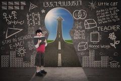 Libro di lettura del ragazzo con la lavagna e la strada di successo Fotografia Stock