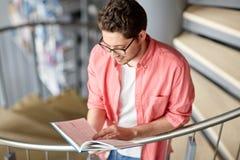 Libro di lettura del ragazzo dello studente o del giovane alla biblioteca Immagine Stock Libera da Diritti
