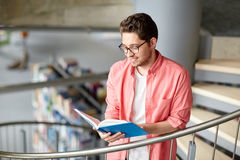 Libro di lettura del ragazzo dello studente o del giovane alla biblioteca Immagini Stock Libere da Diritti