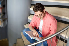 Libro di lettura del ragazzo dello studente o del giovane alla biblioteca Fotografia Stock Libera da Diritti