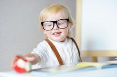 Libro di lettura del ragazzo e mela felici di cibo nel luogo di lavoro Immagini Stock
