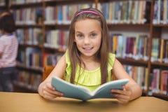 Libro di lettura dell'allievo allo scrittorio in biblioteca Immagini Stock Libere da Diritti