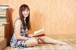 Libro di lettura dell'allievo sul sofà Immagini Stock Libere da Diritti