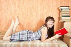 Libro di lettura dell'allievo sul sofà Immagine Stock Libera da Diritti