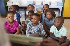 Libro di lettura dell'insegnante ai bambini della scuola elementare nella classe Immagine Stock
