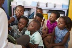 Libro di lettura dell'insegnante ai bambini della scuola elementare nella classe Immagini Stock Libere da Diritti