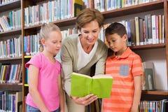 Libro di lettura dell'insegnante con gli allievi alla biblioteca Fotografia Stock Libera da Diritti