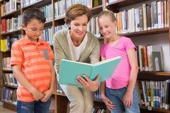 Libro di lettura dell'insegnante con gli allievi alla biblioteca Fotografia Stock