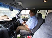 Libro di lettura dell'uomo in automobile Fotografie Stock