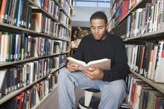 Libro di lettura dell'uomo in biblioteca immagine stock