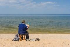 Libro di lettura dell'uomo senior che si siede su una spiaggia Fotografie Stock