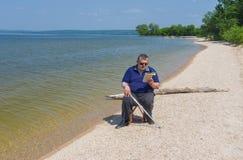 Libro di lettura dell'uomo senior che si siede su una spiaggia del fiume di Dnepr Immagini Stock Libere da Diritti