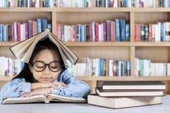 Libro di lettura della bambina in biblioteca Immagine Stock