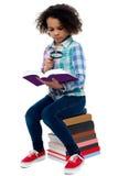 Libro di lettura della bambina facendo uso della lente d'ingrandimento Fotografie Stock