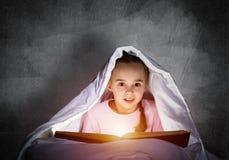 Libro di lettura della bambina a letto fotografie stock libere da diritti